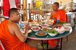 Bangkok, Thailand: Two Monks Eating Lunch Stock Photography