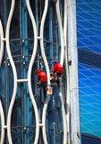 Bangkok, Thailand: Window Washers. Two window washers suspended on cables wash the large panes of glass on a modern office tower on Thanon Phetchaburi in Bangkok Royalty Free Stock Photos