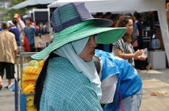 Bangkok, Thailand: Woman at Chatuchak Market. Woman wearing two hats to shade her face from the intense sunlight at the famous weekends-only Chatuchak Market in Stock Photo