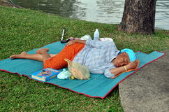 Bangkok, Thailand: Woman Napping in Lumpini Park Royalty Free Stock Image