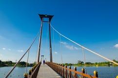 The wooden suspension bridge span that across the small lake at Wareepirom Park. Bangkok, Thailand, The wooden suspension bridge span that across the small lake royalty free stock photography