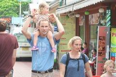 BANGKOK, THAILANDS - 29. April 2018: Vati tragen Tochter auf seinem Hals beim Gehen mit seiner Frau auf Straße Khao San, Bangkok  stockfotografie