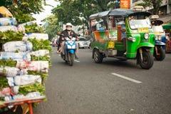 Bangkok Traffic. Bangkok, Thailand - October 19, 2012: A scooter and rickshaws drive through the traffic in Bangkok, Thailand Royalty Free Stock Images