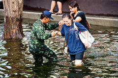 Bangkok Underwater. BANGKOK - NOVEMBER 5: An unidentified soldier helps two unidentified women during the worst flooding in Bangkok, Thailand on November 5, 2011 royalty free stock photography