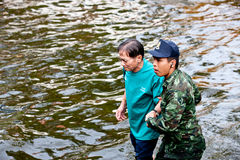 Bangkok Underwater. BANGKOK - NOVEMBER 5: An unidentified soldier helps unidentified man during the worst flooding in Bangkok, Thailand on November 5, 2011 royalty free stock photography