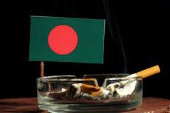 Bangladesch-Flagge mit brennender Zigarette im Aschenbecher lokalisiert auf Schwarzem Stockfotografie
