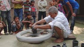 Bangladeschischer Mann demonstriert zum Kindprozeß der Lehmtonwarenproduktion in einer Trachtenmode in Tangail stock footage
