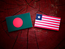 Bangladesh flag with Liberian flag on a tree stump isolated. Bangladesh flag with Liberian flag on a tree stump Royalty Free Stock Photography