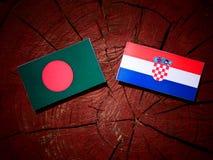 Bangladesh flagga med den kroatiska flaggan på en isolerad trädstubbe Royaltyfria Bilder