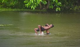 Young boys playing in the water unique photo. Bangladeshi boys playing in the water isolated unique editorial image stock photo