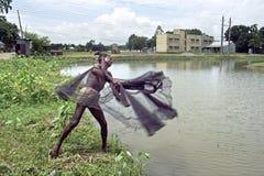 Bangladeshi Fisherman throwing fishing net in a lake Royalty Free Stock Images