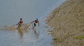 Fishermen working with a nets in the river unique photo. Bangladeshi fishermen are working with a fishing nets in a large river isolated unique editorial image stock photos