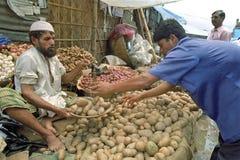 Bangladeshi greengrocer selling potatoes at market. Bangladesh, capital, city Dhaka, in the district Dhanmondi is a Bangladeshi market merchant in his stall with Royalty Free Stock Photos