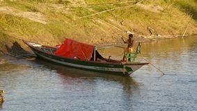 Man on a small boat around a river bank area. Bangladeshi man on a boat around a river bank area isolated unique editorial photo stock photos
