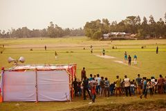 People watching cricket games around a village ground. Bangladeshi people gathered together to watch a cricket game in the village ground unique editorial photo royalty free stock image