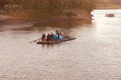 People travelling on a traditional boat in the river unique photo. Bangladeshi people travelling on a boat around a river in the afternoon unique editorial image stock image