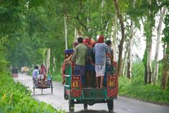 Bangladeshi people travelling on a three wheelers. A group of people riding on a three wheeler vehicle in an urban road in Bangladesh royalty free stock images