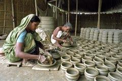 Bangladeshiska kvinnligkeramiker i inre av krukmakeri Arkivfoto