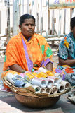 Bangle seller. An Indian women sitting roadside with a basket of bangles in which few bangles are wrapped with newspaper, in the hope of the buyer ,to earn her Stock Images