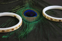 Bangle for the wrist made of conch-shell. Two conch-bangle on peacock feather eye. Stock Image