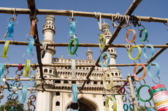 Bangles and Charminar. View looking through a market stall selling bangles towards the landmark Charminar tower in Hyderabad.  The city is famous for making and Stock Images