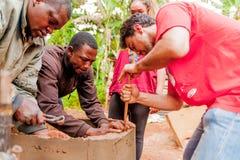 Bangoua, Καμερούν - 8 Αυγούστου 2018: νέος ευρωπαϊκός εθελοντής στο αφρικανικό φρεάτιο νερού του χωριού οικοδόμησης με spatula κα στοκ εικόνα