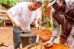 Bangoua, Cameroon - 08 august 2018: young european man in african village doing manual work building water well with concrete in stock photo