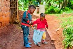 Bangoua, Kameroen - 08 augustus 2018: de Afrikaanse broer helpt zijn kleine zuster die geklede openlucht in handeling van grootmo stock afbeeldingen