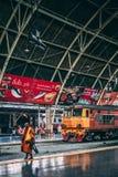 Banguecoque, 12 15 2018: A monge cruza o estação de caminhos de ferro em Banguecoque O trem está esperando passageiros imagem de stock