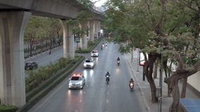 BANGUECOQUE, TAILÂNDIA - CERCA do março de 2017: Tráfego de cidade urbano Carros e bicicletas motorizadas de polícia que acompanh video estoque