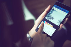 Banguecoque, Tailândia - 23 de agosto de 2017: a mão está pressionando a tela de Facebook na maçã iphone6, meios sociais está usa Imagens de Stock