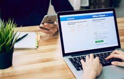 Banguecoque, Tailândia - 23 de agosto de 2017: A mulher está jogando o portátil que mostra o facebook da tela o social o maior e  imagem de stock