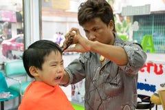 Banguecoque, TAILÂNDIA - 17 de janeiro de 2015: O corte de cabelo e do menino não fazem Foto de Stock