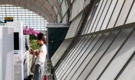 BANGUECOQUE, TAILÂNDIA: 10 de novembro de 2016 - passageiro é o telefone esperto da carga e do uso no aeroporto de Suwannaphum Fotografia de Stock Royalty Free