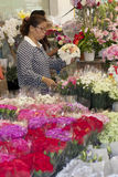 BANGUECOQUE, TAILÂNDIA: 12 de outubro: Mulher que faz o ramalhete da flor na proibição Fotografia de Stock