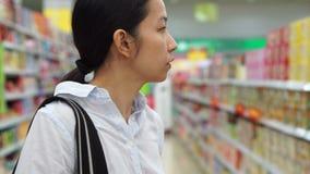 Banguecoque, Tailândia - em abril de 2015 - menina asiática, petiscos andando, da vista e da compra na ilha do supermercado filme