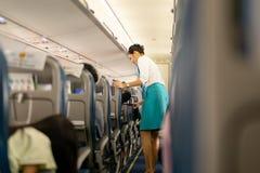BANGUECOQUE, TAILÂNDIA - 27 de agosto de 2018 - alimento e bebidas do saque do aeromoço de Bangkok Airways aos passageiros a bord imagens de stock royalty free