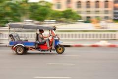 BANGUECOQUE, TAILÂNDIA - 21 de janeiro: Uns três rodaram o táxi de Tuk Tuk ou três rodam a bicicleta em uma rua na capital tailan Foto de Stock