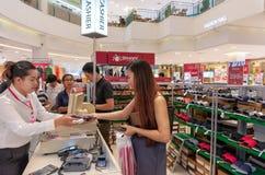 BANGUECOQUE, TAILÂNDIA - 20 DE MAIO: O cliente fêmea não identificado paga por uma compra do produto no caixa em uma venda na ala fotografia de stock royalty free