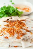 Banh cuon. Vietnamese steamed rice paper with pork, beef and chicken insied with fresh fried onions tofu,  and meat ham -  patev, egetables and coriander Stock Image