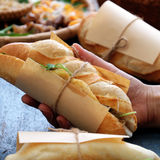 Banh mi, Vietnamese bread. Woman hand make banh mi thit or Vietnamese bread, famous street food from raw material: pork, ham, pate, egg and fresh herbs as royalty free stock photography