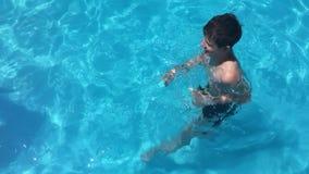 Banhe na água da associação as crianças menino e a natação da menina na associação caçoam o jogo do vídeo de movimento lento vídeos de arquivo