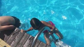 Banhe na água da associação as crianças menino e a natação da menina na associação que joga o vídeo de movimento lento caçoam video estoque