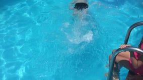 Banhe na água da associação crianças menino e crianças da menina que nadam na associação que joga o vídeo de movimento lento video estoque