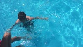 Banhe na água da associação crianças menino e natação da menina na associação que joga o vídeo de movimento lento das crianças filme