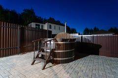 Banheira de hidromassagem de madeira rural da água com jarda do jardim das escadas noite e céu estrelado imagens de stock royalty free