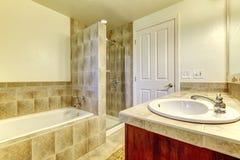 Banheiro com cuba, o chuveiro pequeno e os armários de madeira. Fotografia de Stock Royalty Free