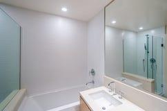 Banheiro com dois dissipadores e os armários de madeira imagem de stock