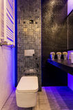 Banheiro escuro iluminado com luzes azuis Fotos de Stock