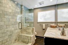 Banheiro luxuoso com o chuveiro branco e cinzento do mármore e do vidro fotos de stock royalty free